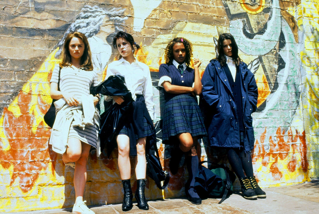 A still from 'The Craft'. Sarah (Robin Bailey), Nancy (Fairuza Balk), Rochelle (Rachel True) and Bonnie (Neve Campbell) stands against a graffiti-ed wall. Sarah looks like the girl next door wearing a tennis dress, fair skin and long dark hair. Nancy is gothic, wearing her school uniform and extremely pale. Rochelle, has dark skin and is also wearing her uniform. Bonnie is wearing her uniform, a massive parka jacket swamping her figure and dark hair covering her face.