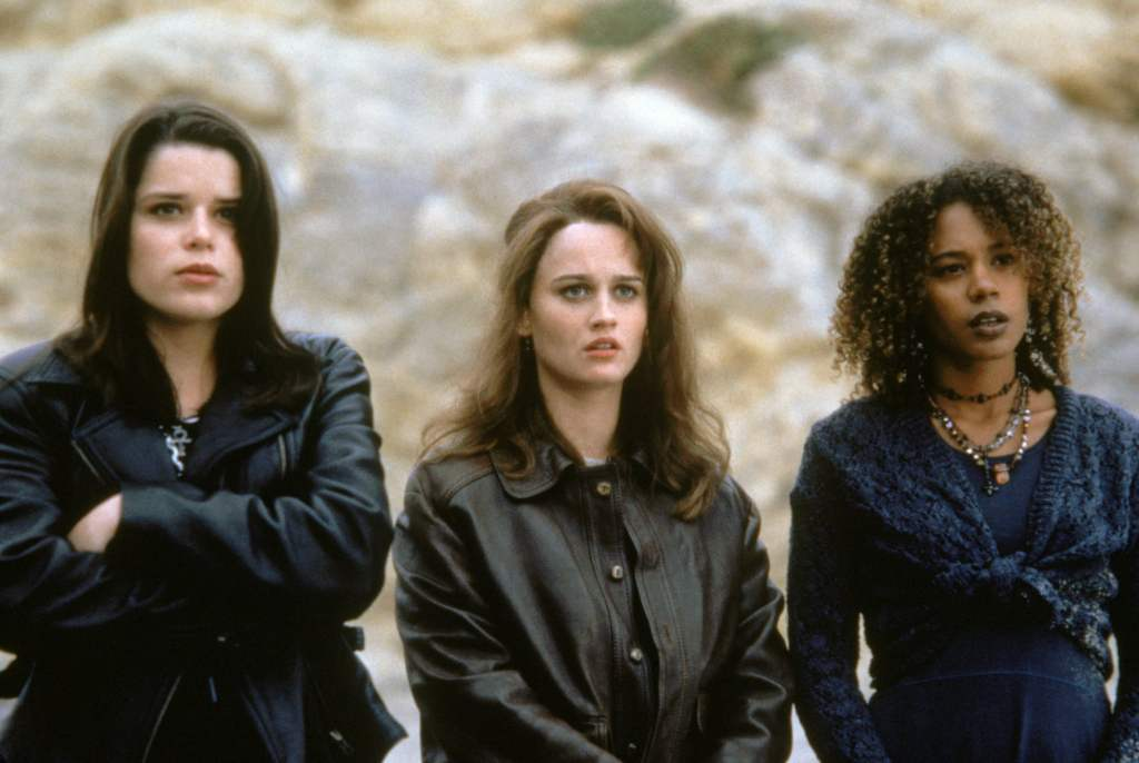 A still from 'The Craft'. Bonnie (Neve Campbell), Sarah (Robin Tulley) and Rochelle (Rachel True) are shown here in a mid-shot. All the girls are wrapped up in fall clothing in dark tones of black and brown leather and Rochelle in a navy knit cardigan. THey are outside and the background of the image looks like a rockface.