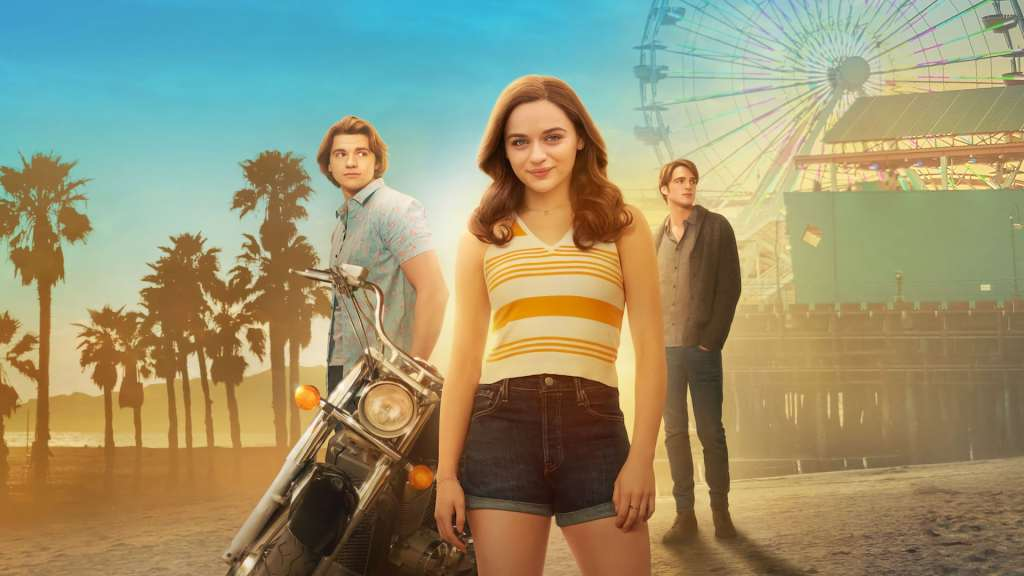 A promotional image from 'The Kissing Booth 2'. Joey King is the centre front with dark hair an orange striped V-neck top and denim shorts. Behind her two boys, clearly love rivals stand gazing off into the distance. They are similar looking white boys with floppy dakr blonde hair. A motorbike is also behind Joey and a fairground can palm trees can be seen in the distance.