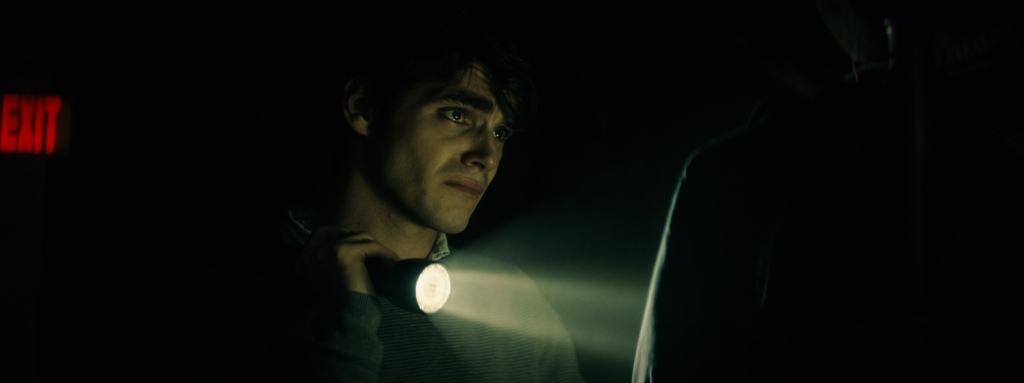 A still from'The Oak Room'. Steve (RJ Mitte) is shown in close up here shrouded in darkness aside from the light coming from his torch. His cheekbones are lit up and angular, a heavy set and dark brow furrowed in upset and concern, looking towards an object just outlined by the torch's glow.