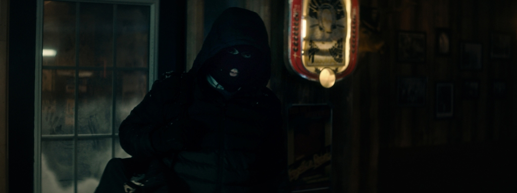 A still from 'The Oak Room'. A balaclava clad and hooded man walks into a bar dressed completely in black, aside from the slight hint of a white collar peeking out. His presence is threatening. Frost on the bar's windows show that it is a cold winter's night, the walls are wooden and there is taxidermy and framed photos adorning the gloomy walls.