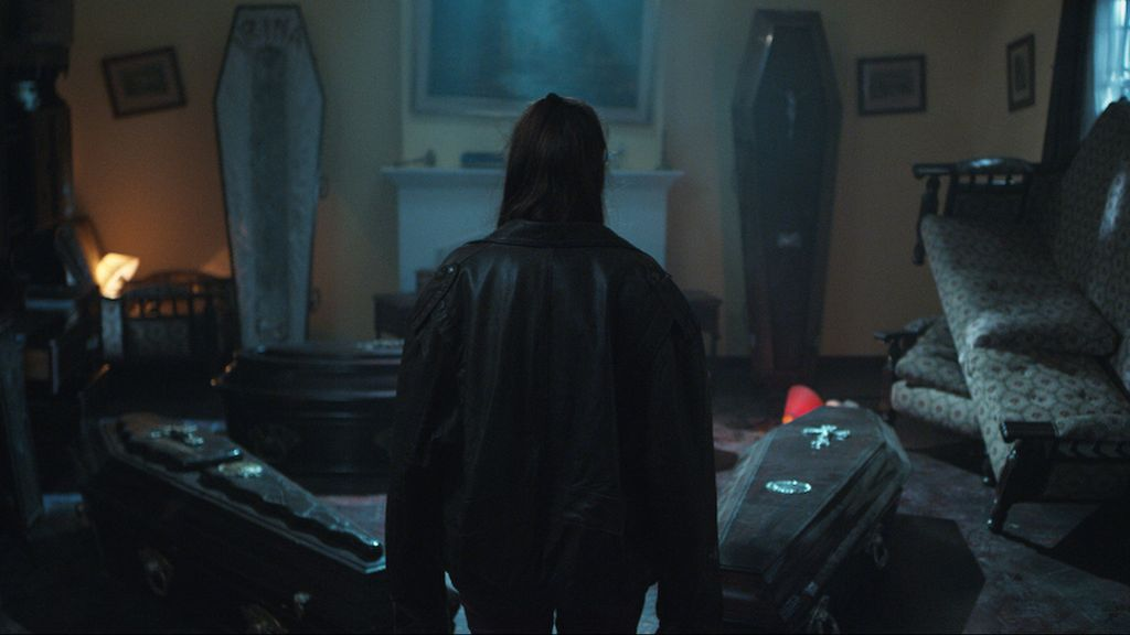 A still from 'The Undertaker's Home'. Irina (Camila Vaccarini) is shown here in a wide shot with her back to the camera, a heavy leather jacket over her back. She is in a room filled with coffins, most of them sealed but one open and empty. It is a scene of carnage, the sofa and armchair are flipped in the air and lamps have fallen from their tables.