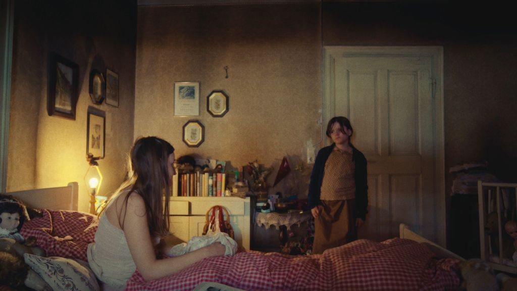 A still from 'Time of Moulting'. Young Stepanie (Zelda Espenschied) stands in a bedroom against a white door, she is wearing dark and grab clothing with a blue cardigan. She is looking towards her mother (Freya Kreutzkam) who is sat in the bed in her nightgown. Her mother is surrounded by stuffed animals and the room is generally adorned with childhood toys and paraphernalia. It is a gloomy scene. .