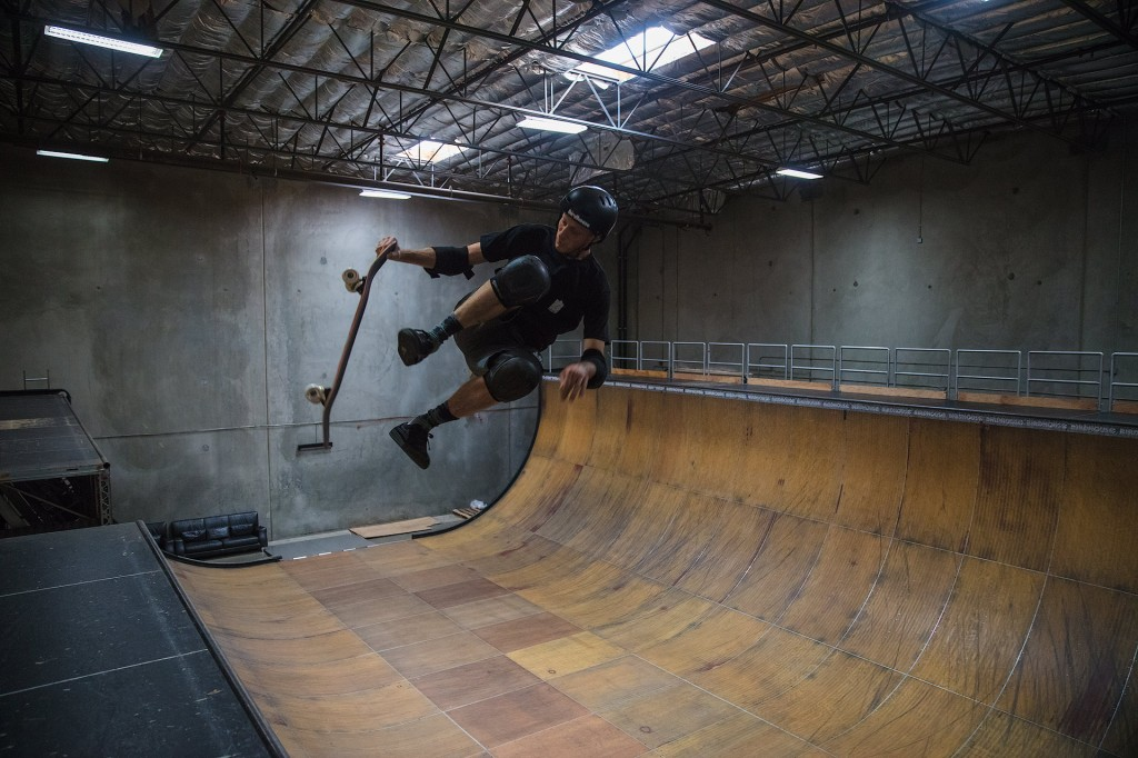 Skateboarder Tony Hawk is shown here skating a vert ramp, pictured mid air with his feet off the board, and only one hand grabbing the board. It looks like an old warehouse behind him and he is fully padded up wearing a helmet.
