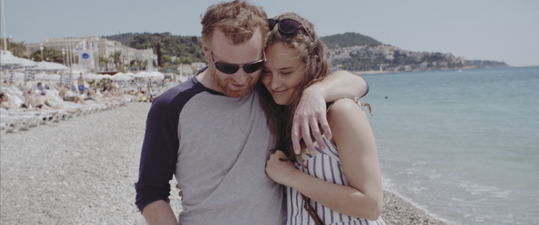 A still from 'Tracks'. Chris Willoughby and April Pearson on the beach in Nice, walking with arms around each other
