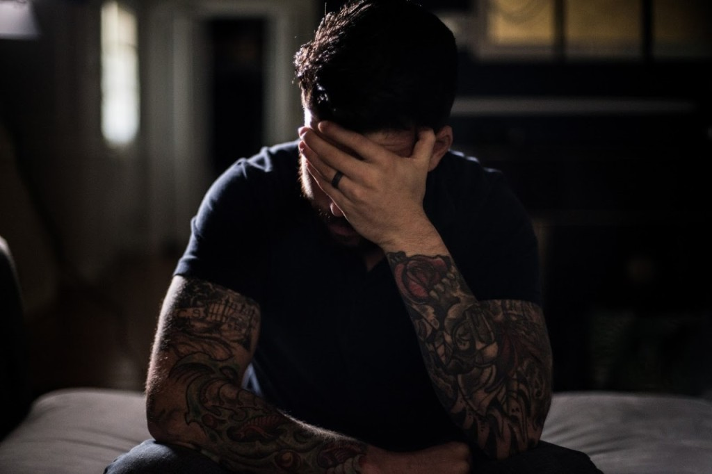A still from documentary 'Unprescribed'. A man sits on the edge of a bed in a room drowned in shadow. He has his hand to his face covering it in a sense of frustration or shame. He is heavily tattooed on his arms and wears a black wedding band on his left hand. His hair is dark and his t-shirt is black.