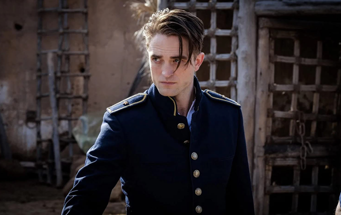 A still from 'Waiting for the Barbarians'. Officer Mandel (Robert Pattinson) is shown in a mid-shot wearing his blue military uniform with gold trim. The top two buttons of his jacket are undone and his hair is slicked back apart from two strands hanging down his face. He has his jaw clenched as he looks over to something off-screen.