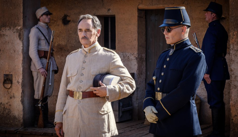 A still from 'Waiting for the Barbarians'. The Magistrate (Mark Rylance) stands in a tan linen uniform next to Colonel Joll (Johnny Depp) who is wearing a blue military uniform with gold trim, and a blue hat. He weats dark sunglasses. Both men are unarmed. Two other soldiers stand guarding the door to the building behind them.