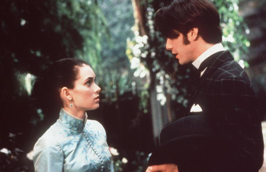 A still from 'Bram Stoker's Dracula'. Mina (Winona Ryder) and Jonathan (Keanu Reeves) are shown in close up facing one another. Jonathan towers over Mina and wears a black Victorian suit, carrying his bowler hat under his arm, His dark hair covers his eyes. Mina is wearing a high necked blue Victorian bodice, her long dark hair pulled back into a bun on the back of her head. She looks at Jonathan with concern.