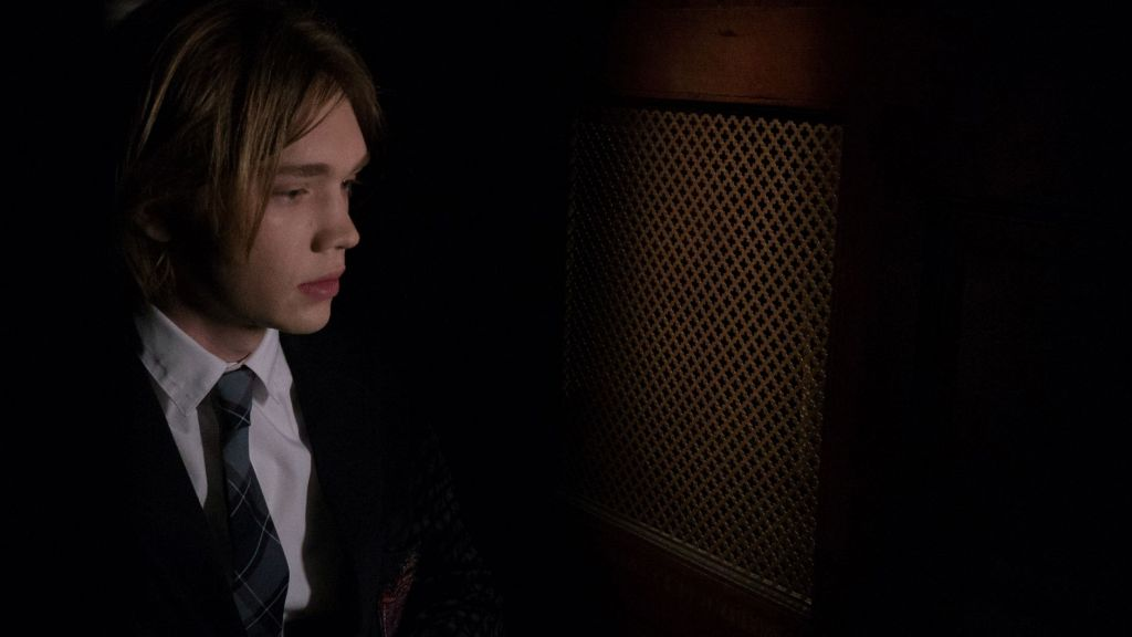 A still from 'Words on Bathroom Walls'. Adam (Charlie Plummer) is seen here seated in a confessional wearing his school uniform. It is a black blazer and a blue and black plaid tie with a white shirt. His blonde hair is quite long to his chin, framing his youthful face.