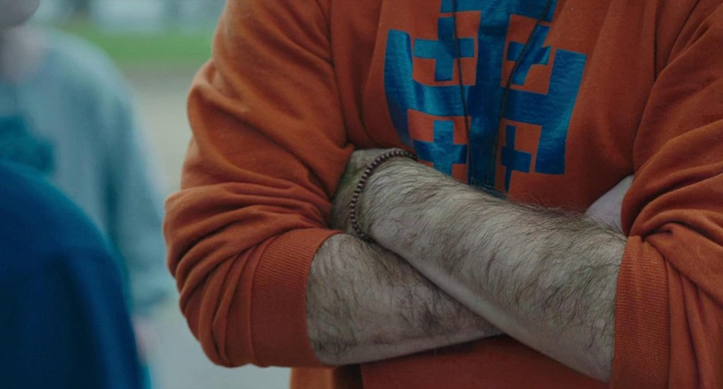 A still from 'Yes God Yes'. A man's arms are seen in close up crossing across his chest, they are incredibly hairy. He is wearing an orange sweatshirt with a blue logo on, you cannot see his face.