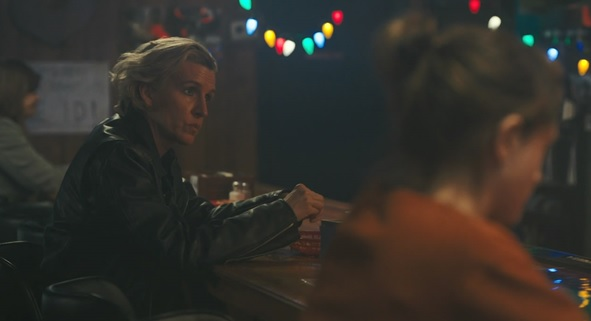 A still from 'Yes God Yes'. A woman in her 30s/40s sits at a bar, she has bleach blond short hair and a leather jacket, she looks like she is about to speak, Natalia Dyer is out of focus at the end of the bar with her back to camera.