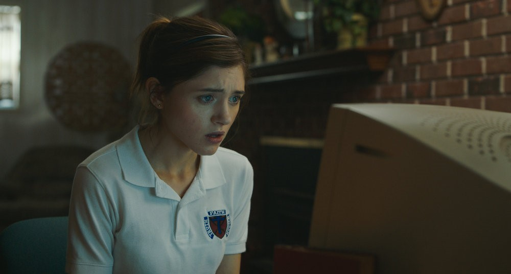 A still from 'Yes God Yes'. Natalia Dyer is wearing a Catholic school uniform, staring at her desktop PC screen, she has her hair pulled back into a ponytail with a headband on. Behind her is a mantle piece filled with trinkets and a fireplace beneath.