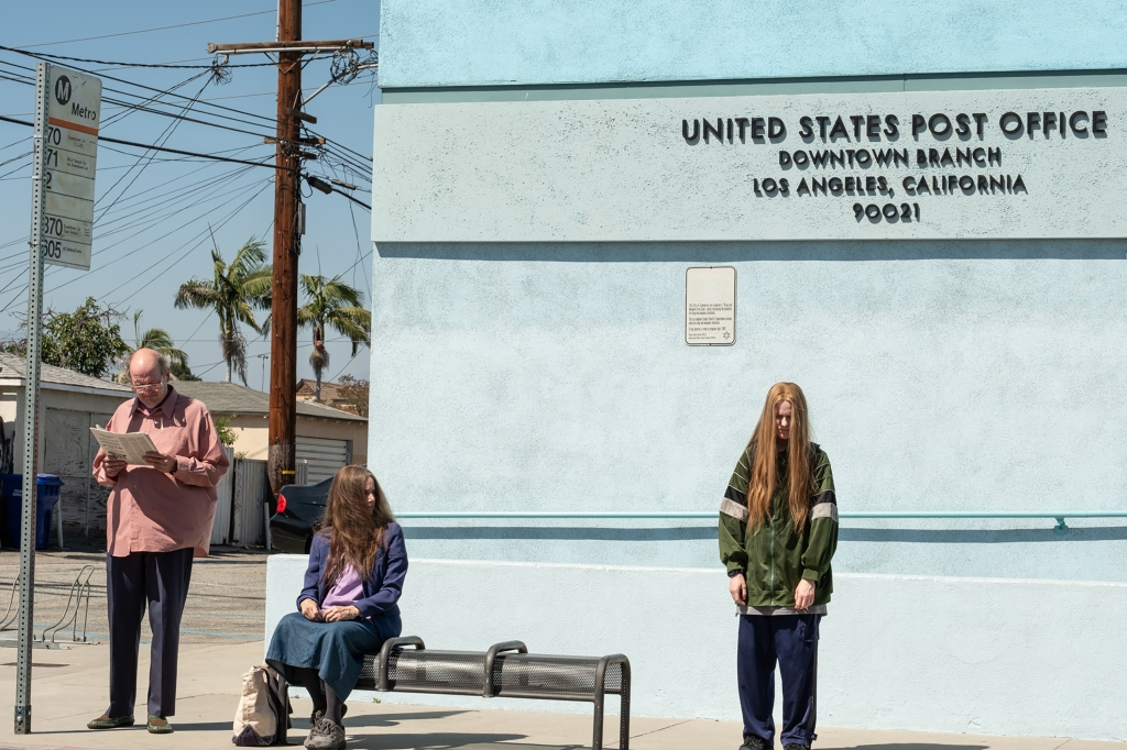 Robert (Richard Jenkins), Theresa (Debra Winger), and Old Dolio (Evan Rachel Wood) are seen standing awkwardly from each other again a light blue coloured post office. Robert  is standing and reading a newspaper, as he wears a muted salmon coloured shirt and dark trousers. Theresa is sitting on a bench, her face obstructed by her long ashy brown hair. Old Dolio has long strawberry blonde hair hiding her face as she looks downwards, she is wearing an oversized khaki green tracksuit.