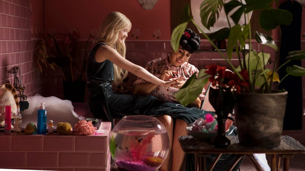 A still from 'A Mermaid in Paris'. A memaid sits on the edge of a bath in a bright pink room. A woman sits beside her, painting her fingernails. Plants and nick nacks litter every available surface.