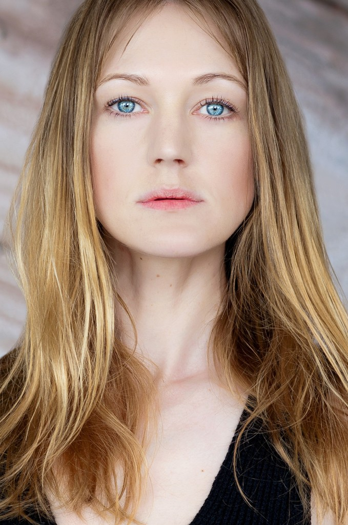 Headshot of Azura Skye. She is a young white woman, with fair skin and blue eyes with long dark blonde hair, gazing directly at the camera.