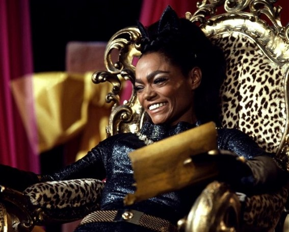 A still from the TV show 'Batman'. Catwoman (Eartha Kitt) is shown in close-up, grinning with blindingly white teeth, sat on a gold and leopard skin throne. She is a beautiful Black woman with heavy eyebrows and a black bouffant hairstyle with added cat ear hairband. Her catsuit is black and glittery with a gold chain around her neck.