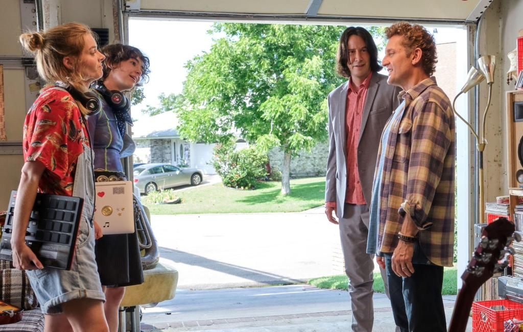 A still from 'Bill and Ted Face the Music'. Bill (Alex Winter) and Ted (Keanu Reeves) stands in a garage in a suburban neighbourhood with their respective daughters Billie (Brigette Lundy-Paine) and Thea (Samara Weaving).Billie stands opposite Ted, she is wearing big headphones and a blue mesh crop top and oversized black shorts. She carries her laptop under her arm. Ted wears a grey suit with a pink shirt underneath, Thea stands opposite Bill. She wears denim short dungarees and a fish print shirt, carrying a synthesiser under her arm. Bill wears a purple and cream plaid shirt and jeans.