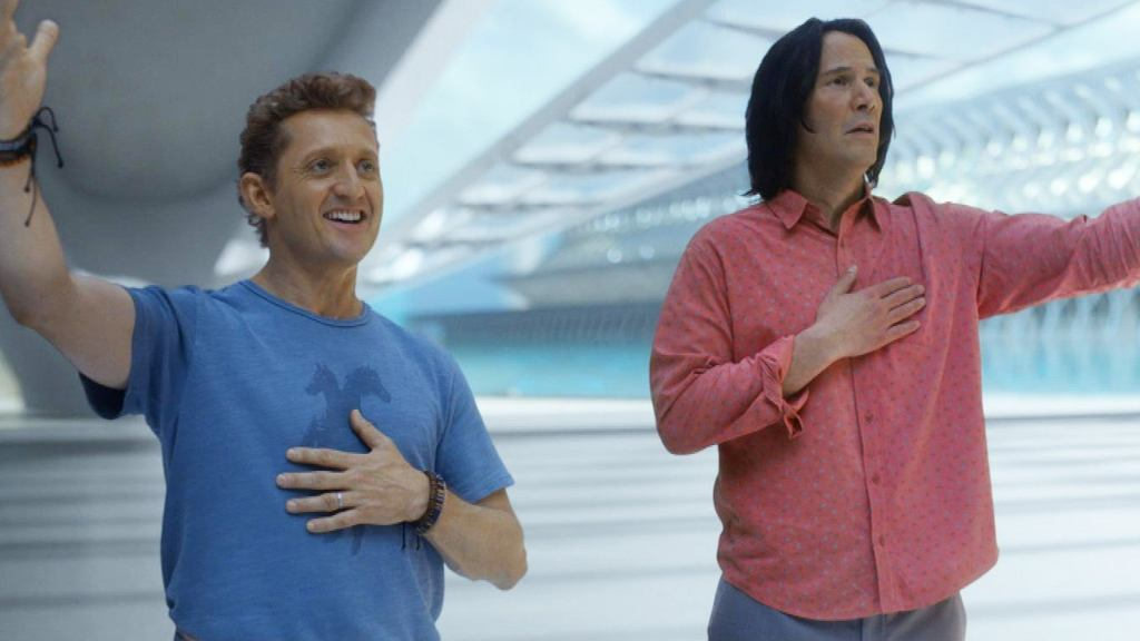 A still from 'Bill and Ted Face the Music'. Bill (Alex Winter) and Ted (Keanu Reeves) stand in mid shot both standing in a futuristic looking arena space. Bill is on the left with coiffed blonde short hair and bright white teeth, he wears a blue t-shirt and bracelets on each wrist. He has his left hand on his chest and his right hand outstretched to the sky. Ted is in the same pose . He wears a pink long sleeved shirt and has dark shaggy hair.