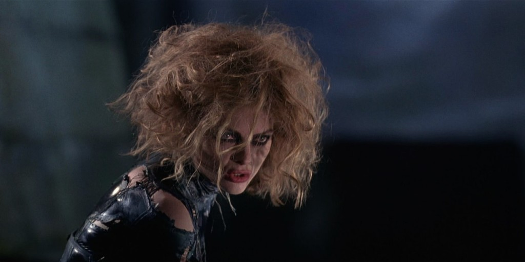 A still from 'Batman Returns'. Catwoman (Michelle Pfieffer) is shown against a dark backdrop to the left of the image, in close up. Her blonde hair is matted and scraggly all over her head and face, sticking up all angles. You can just see dark eyeshadow peeking out from under the hair and a pink lipstick. Her homemade leather patchwork catsuit is ripped and torn at the shoulder and back.