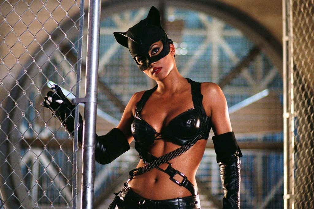 A still from 'Catwoman'. Catwoman (Halle Berry) stands in the doorway of a metal chainlink fence. She is a Black woman, very athletic. She wears a skimpy leather and PVC outfit consisting of a bra and wrap around chain belts, elbow length black gloves with white claw tips and a latex cat mask that covers her scalp. She has heavy eyeliner on and red lipstick.