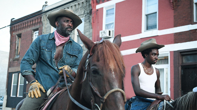 Still from Concrete Cowboy. Idris Elba and Caleb McLaughlin sit on top of two horses in a street. They are both wearing cowboy hats and dressed in denim.