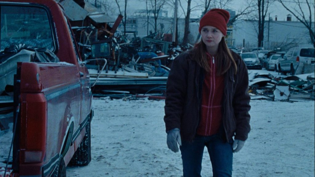 A still from 'Holler'. Ruth (Jessica Barden) stands in a snowy scrap yard next to a red truck. she is wrapped up for the winter, in jeans, a fleece jacket and puffy coat with gloves and red hat. the image is drenched in blue and looks cold.