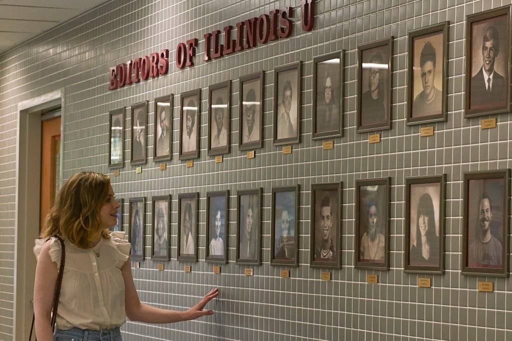 A still from 'I Used to go Here'. Kate (Gillian Jacobs) is shown to the left hand side of the image, she is pale and in her 30s with shoulder length blonde, wavy hair. She wears a cream, short sleeved blouse and jeans. She is walking through a corridor looking at photos on a wall that says 'Editors of Illinois U'