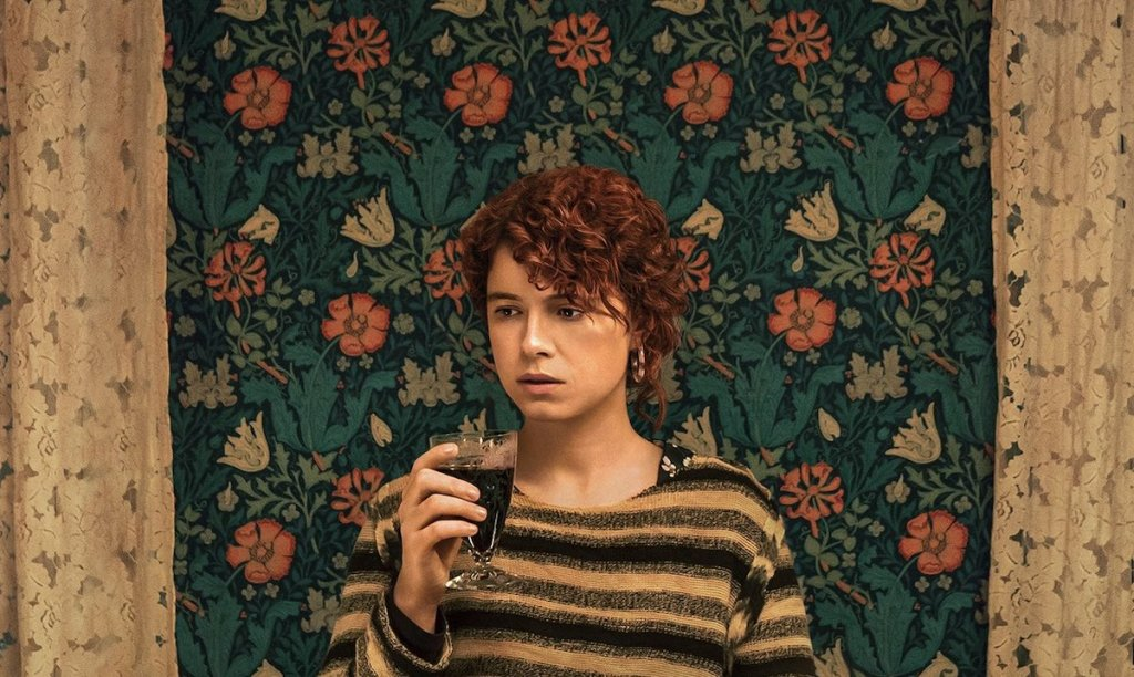 A still from 'I'm Thinking of Ending Things'. The Young Woman (Jessie Buckley) stands in front of a garish green floral wallpaper, flanked by even more garish floral lace curtains. The woman has red curly hair and wears a striped jumper, she is holding a glass of wine and looking unsure.