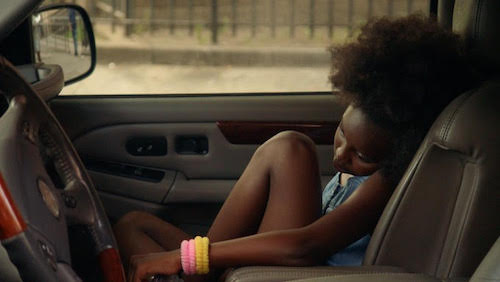 Still from In Sudden Darkness. A young girl sits, hunched over in a car.