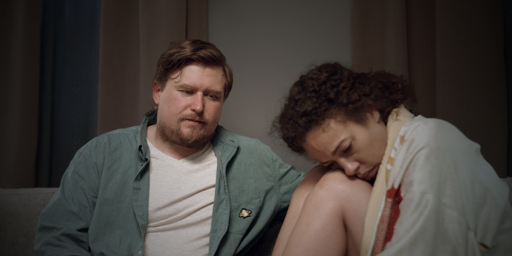 A still from 'Inez & Doug & Kira;. Doug (Michael Chernus) is an overweight man in his 30s, with strawberry blonde hair and a goatee. He is wearing a blue shirt open with a white t-shirt underneath. He is sat on a sofa with Kira (Talia Thiesfield), consoling her over the death of her sister. Kira is a mixed race woman in her 30s, slim with natural hair. She has a dressing gown on and her knees pulled up around her chest, crying.