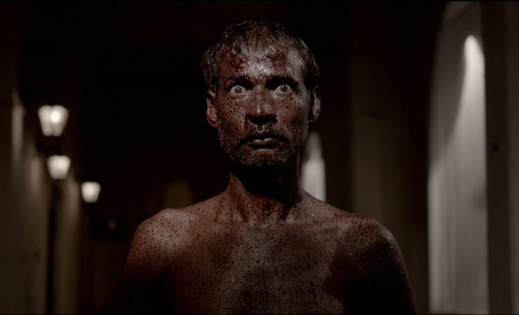 A still from 'Kriya'. Neel (Noble Luke) stands in close up in centre frame. He is a dark skinned, thin young man with dark hair and a small beard/moustache. He has a bare chest and is covered completely in blood. The whites of his eyes stand out in the image as his eyes are wide open.