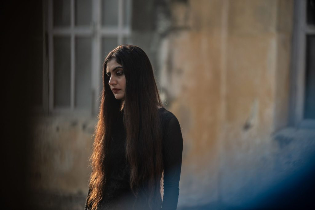 A still from 'Kriya'. Sitara (Navjot Randhawa) stands in a mid-shot looking out to the left of the frame. She is a beautiful woman with dar, heavy makeup and incredibly dark, long hair. She wears a black dress and stands in front of what looks like an abandoned building. She seems contemplative.