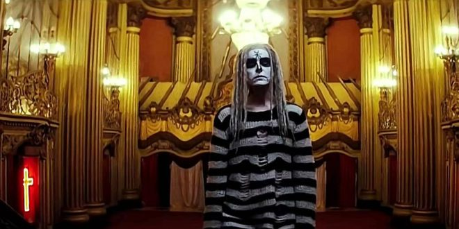 A still from 'Lords of Salem'. Heidi (Sherri Moon Zombie) stands in a church shown in mid shot. She is completely transformed into a skeletal figure wearing a black and white striped jumper, white dreadlocks and skeleton face paint.