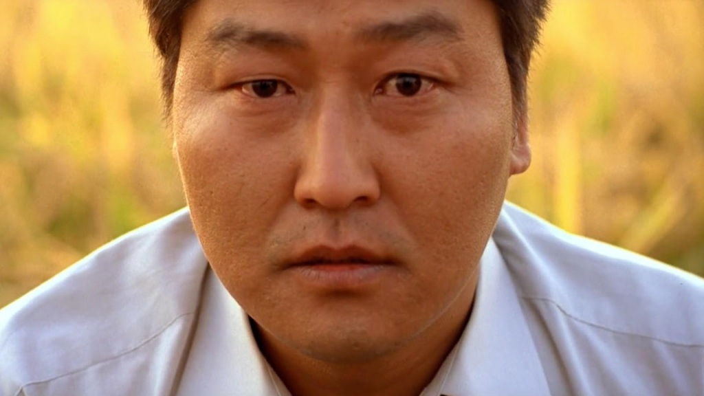 A still from 'Memories of Murder'. Park Doo-man (Song Kang Ho) is shown in close-up sitting in a cornfield. He is staring directly at the camera with a vacant, yet slightly confused expression. He wears a white shirt, is clean shaven, in his 30s/40s with dark had and dark eyes.