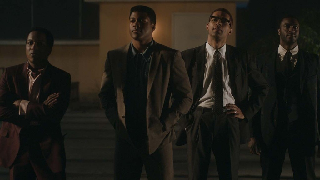 (L to R) Leslie Odom Jr, Eli Goree, Kingsley Ben-Adir, and Aldis Hodge standing on a a hotel roof top. They all glance at the view from the roof.