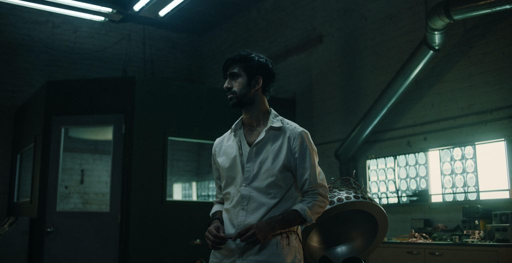 A still from 'Minor Premise'. Ethan (Sathya Sridharan), a neuroscientist, stands centre frame in his laboratory in a white shirt. He looks sweaty and dishevelled.