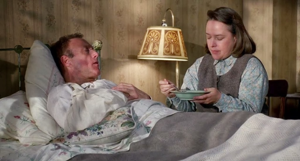 A still from 'Misery'. Paul Sheldon (James Caan) is in bed, wrapped in dated floral bedsheets, being tended to by Annie Wilkes (Kathy Bates). She sits on a wooden chair by the bedside, a lamp lighting the scene next to them. She is feeding him something from a bowl. He wears a nightshirt and she wears a grey long sleeved shirt and dark grey pinafore, with short brown hair.