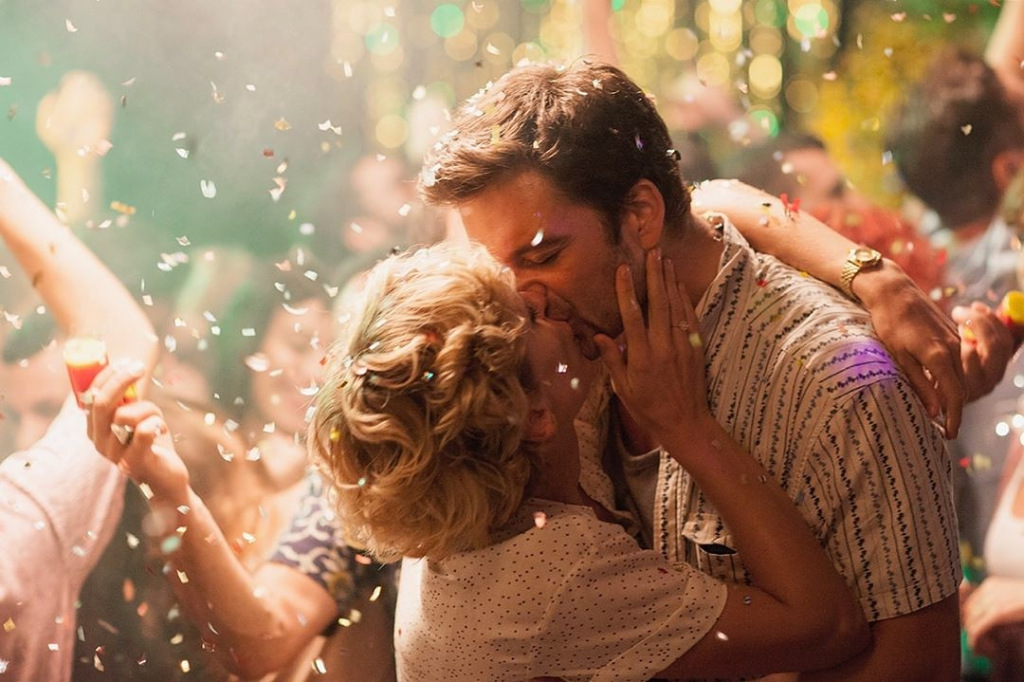 A still from 'Monday'. Denise Gough and Sebastian Stan kissing at a party with confetti falling.