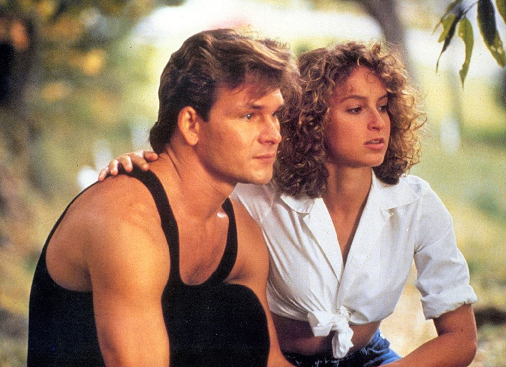 Patrick Swayze and Jennifer Grey in Dirty Dancing (1987). Johnny (left) and Baby (right) are a young couple crouched together in the trees, Baby's arm around Johnny's shoulder. They are both wearing their dance clothes - he in a black vest and pants, and she in a white collared shirt with the sleeves rolled up and tied in a knot at the front, with blue denim shorts.