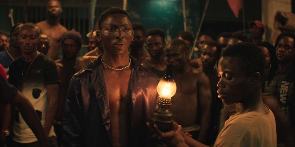 Still from Night of the Kings. A young man stands in front of a crowd of men looking scared, wearing a necklace and another young man holds a lamp up to him.