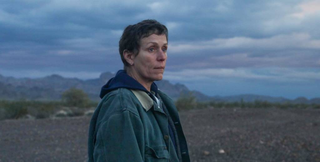 A still from 'Nomadland'. Frances McDormand stands in the centre frame, in profile against a backdrop of rocky mountains and bushland. She has short dark cropped hair and a blue hoodie with a dark green denim jacket over the top.