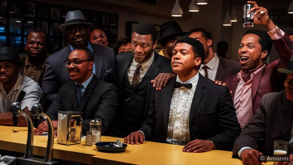 Still from One Night in Miami. Aldis Hodge, Leslie Odom Jr., Eli Goree and Kingsley Ben-Adir are in front of a bar, looking excited and also pensive - surrounded by other paterons.