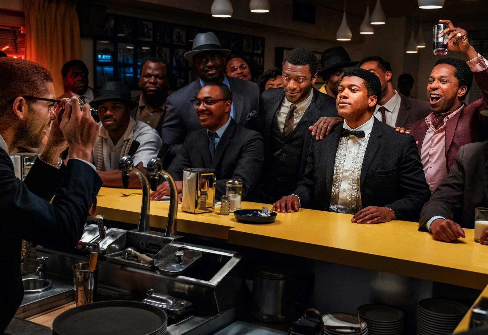 A still from 'One Night In Miami'. Kingsley Ben-Adir as Malcolm X on the bartender side of a bar taking a photograph of a group of Black American men. Right-center is Aldis Hodge, Eli Goree, and Leslie Odom Jr as Jim Brown, Cassius Clay, and Sam Cooke
