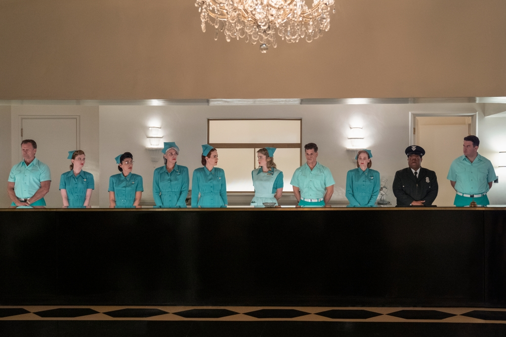 A still from 'Ratched'. The staff of the Lucia State Mental Hospital are lined up behind a help desk. Mainly consisting of female nurses, one being Ratched (Sarah Paulson) and 3 male attendants and a security guard. All the people bar the security guard are wearing minty green outfits in a 1940s style.