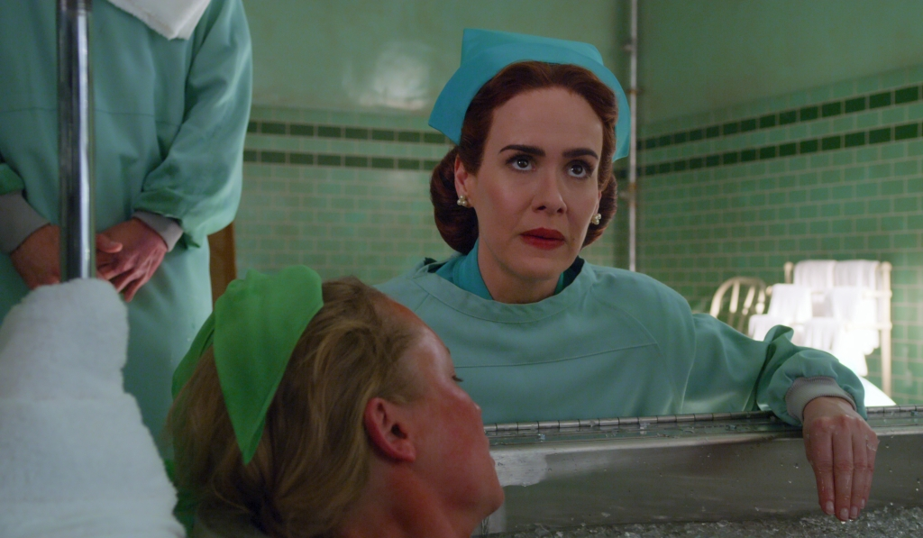 A still from 'Ratched'. Mildred Ratched (Sarah Paulson) is shown in close-up leaning over an ice bath with a female patient inside. Ratched wears green scrubs and hair hair pulled back into a net, she is very glamorous with a full face of make-up. The tiles behind her are also green, its a 1940s setting.