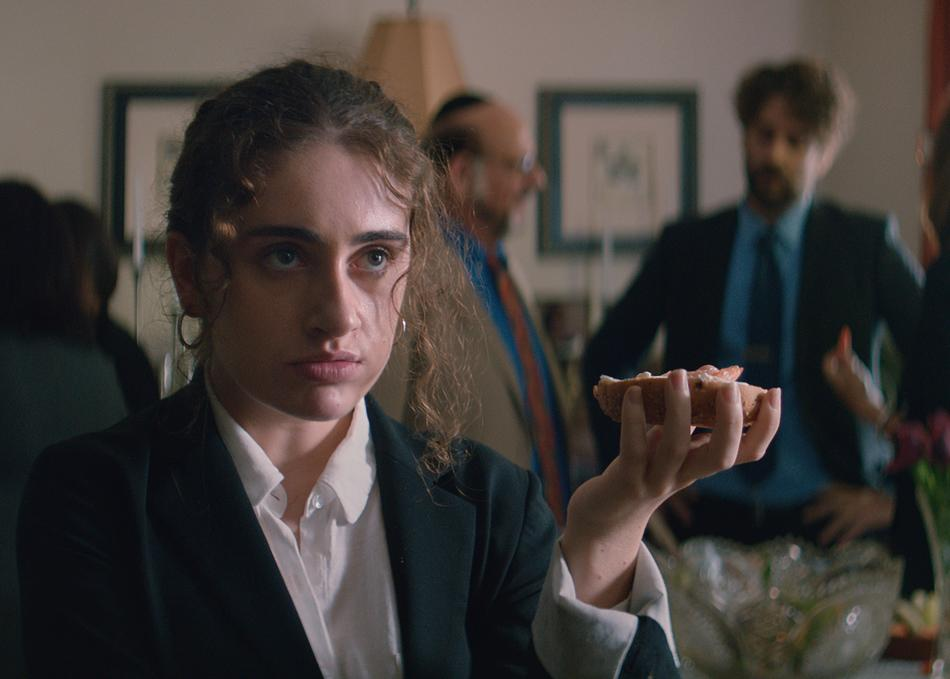 Still from Shiva Baby. Rachel Sennott, wearing a black blazer and white shirt holds up a bagel in her left hand.