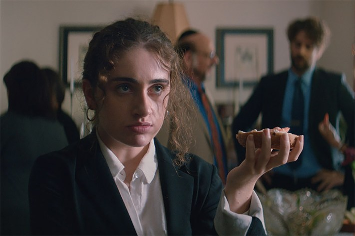 A still from 'Shiva Baby'. Danielle (Rachel Sennott) is standing in a room at a Shiva. She is shown in close-up, shes in her 20s with dark eyebrows and brown curly hair pulled into a ponytail. She wears hoop earrings, a white shirt and black blazer, she holds what looks like a bagel in her hand, she looks angry.
