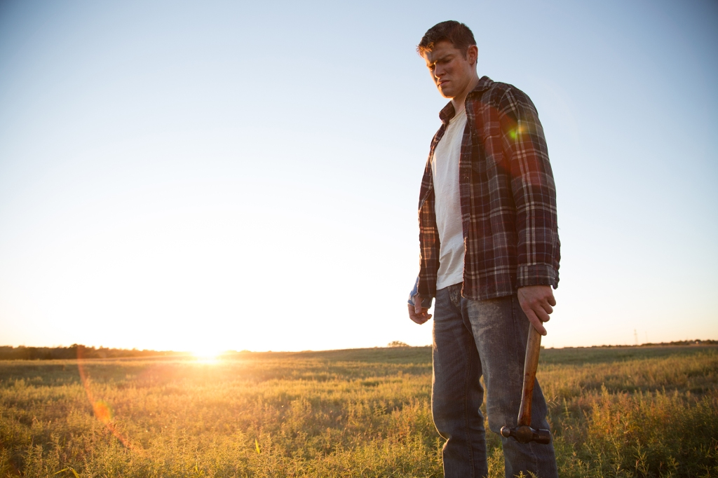 A still from 'All Roads to Pearla'. Brandon (Alex MacNicoll) stands in a field during golden hour, he stands to the right of the image, shown in a full length shot. He is a young, white man with short hair and wearing typical American male clothing: jeans, t-shirt and open plaid shirt. He holds a hammer in his left hand and is staring at the ground.