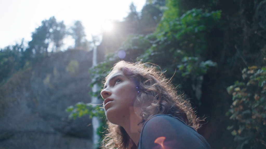 A still from 'Sophie Jones'. Sophie (Jessica Barr) is shown here in closeup, centre frame towards the bottom of the image, we can just see her head in profile and her shoulder. She is a teenange girl with curly cark blonde hair and a pale complexion. Surrounding her is lots of trees and nature. she looks up to the sky,
